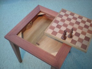 The top of the table lifts out and you can store the chess pieces under it. To lift the top out there is a simple button on the underside of the table